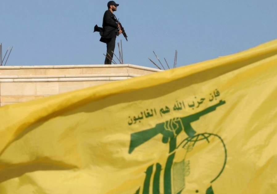 A Hezbollah member carries his weapon on top of a building in Bekaa Valley