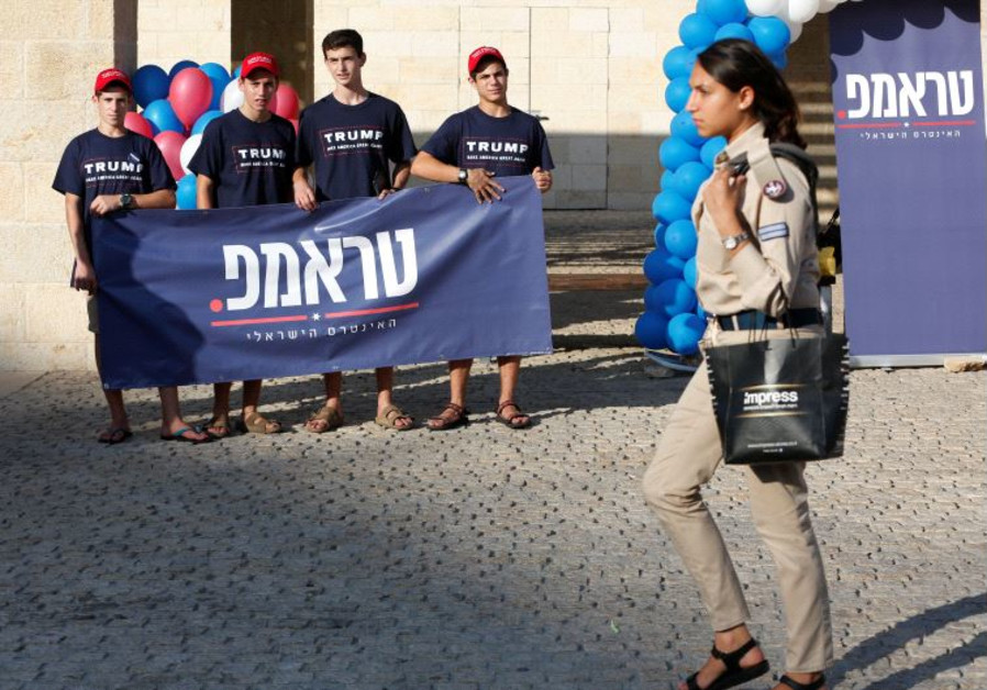 An Israeli soldier walks past members of the US Republican party's election campaign team in Israel,