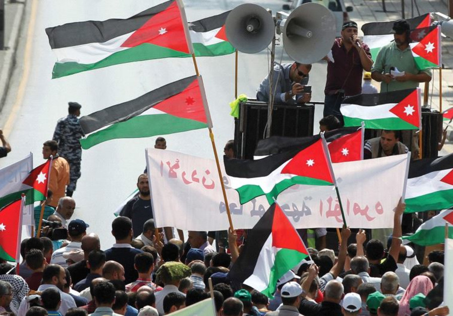 PROTESTERS IN Jordan hold Jordanian and Palestinian flags as they march in protest against Israel.