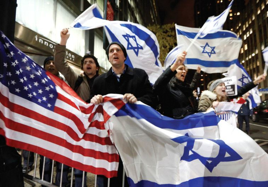 People wave American and Israeli flags‏