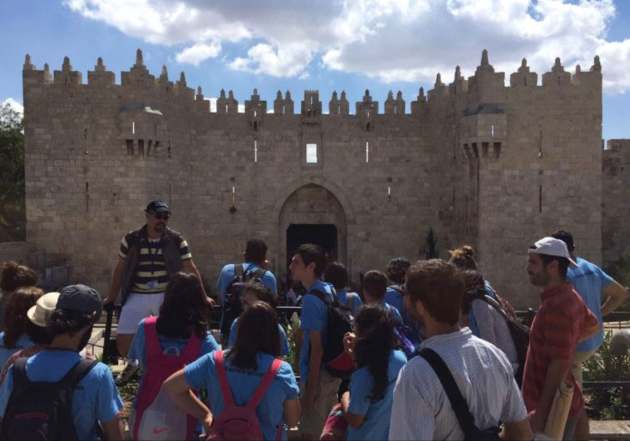 YOUNGSTERS ON the Kids4Peace Jerusalem walk pause in front of Damascus Gate on Friday.