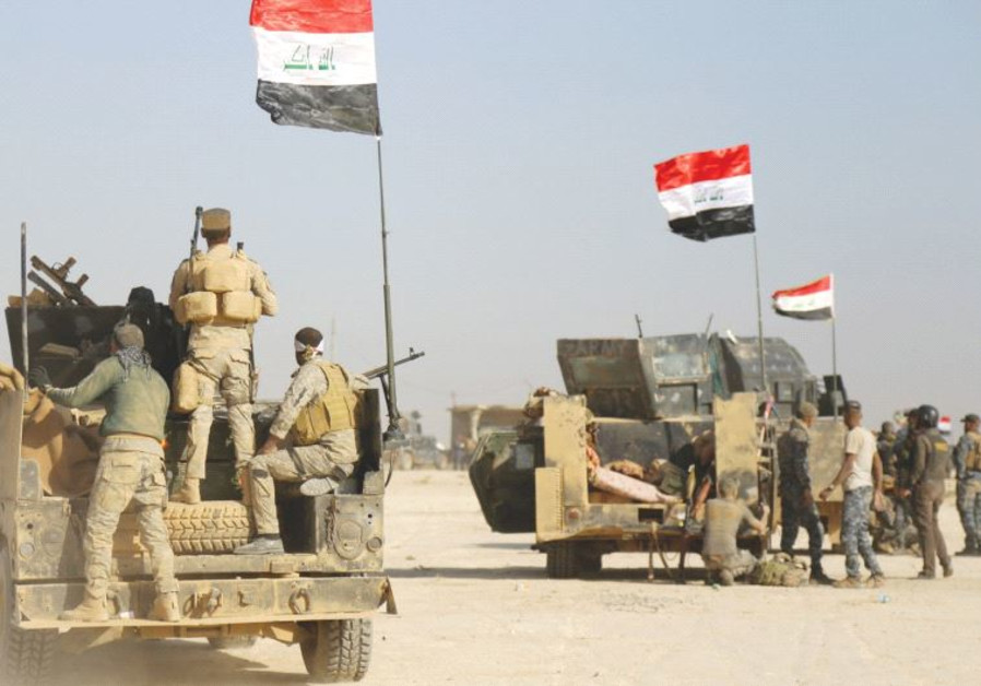 IRAQI FORCES advance in Qayara to attack Islamic State in Mosul yesterday.
