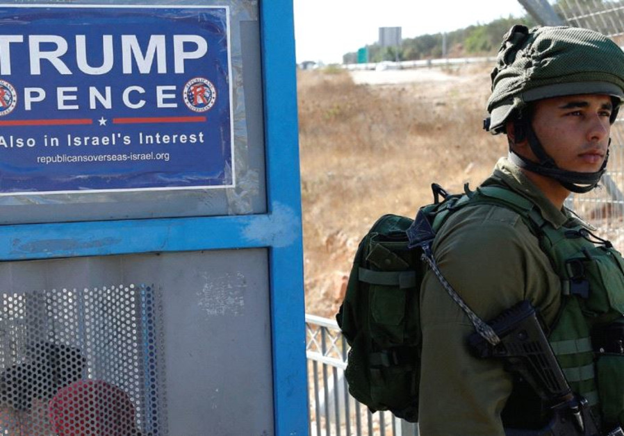 A soldier stands next to a bus stop with a pro-Trump poster near the West Bank Jewish settlement of