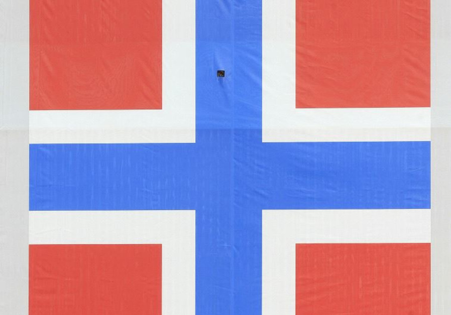 A woman cycles past a banner of the Norwegian flag attached to a warehouse in Oslo, Norway.