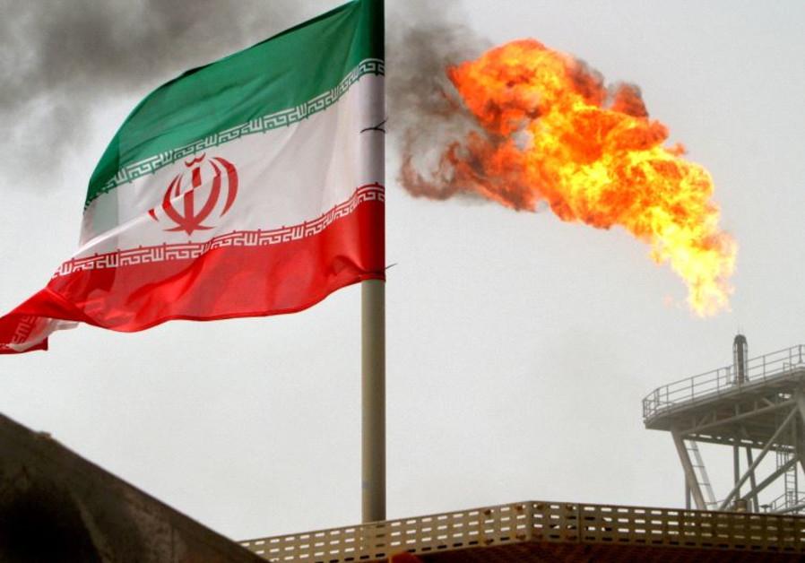 A gas flare on an oil production platform in the Soroush oil fields is seen alongside an Iranian fla