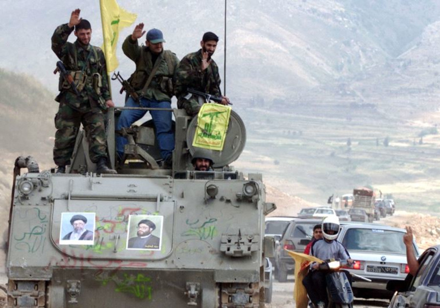 Pro-Iranian Hezbollah guerrillas, riding on an APC M113 used by pro-Israeli militiamen, wave to pass
