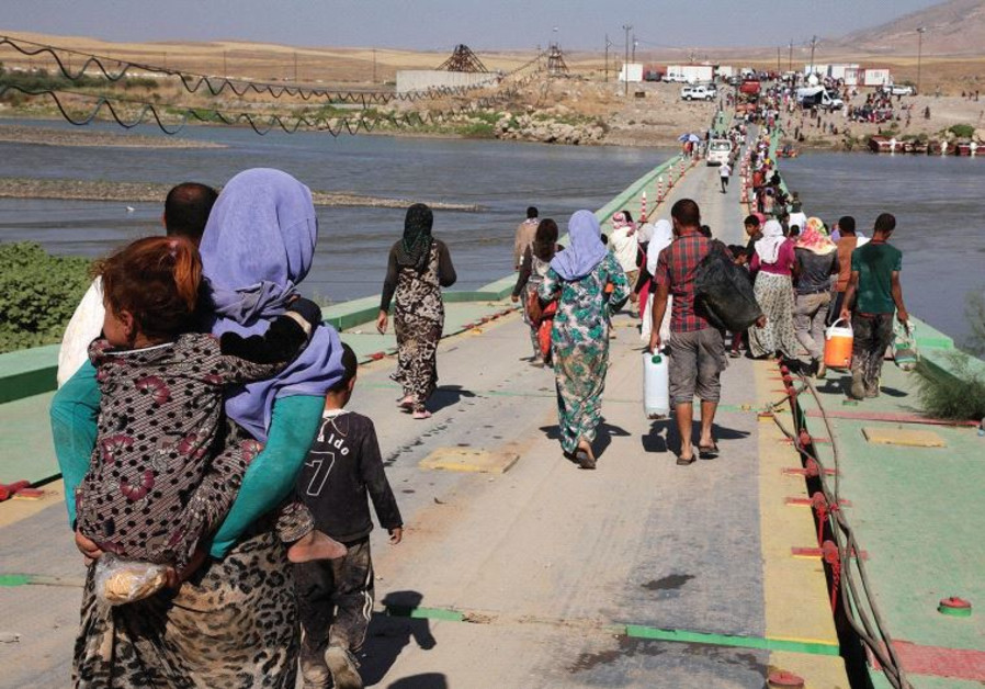 YAZIDI WOMEN and men flee Islamic State on August 10, 2014 in northern Iraq. Many were captured by I