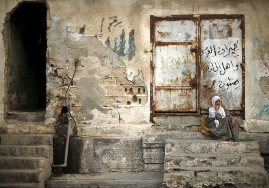 A Palestinian woman sits outside her house as she escapes the heat during a power cut at Shatti (bea