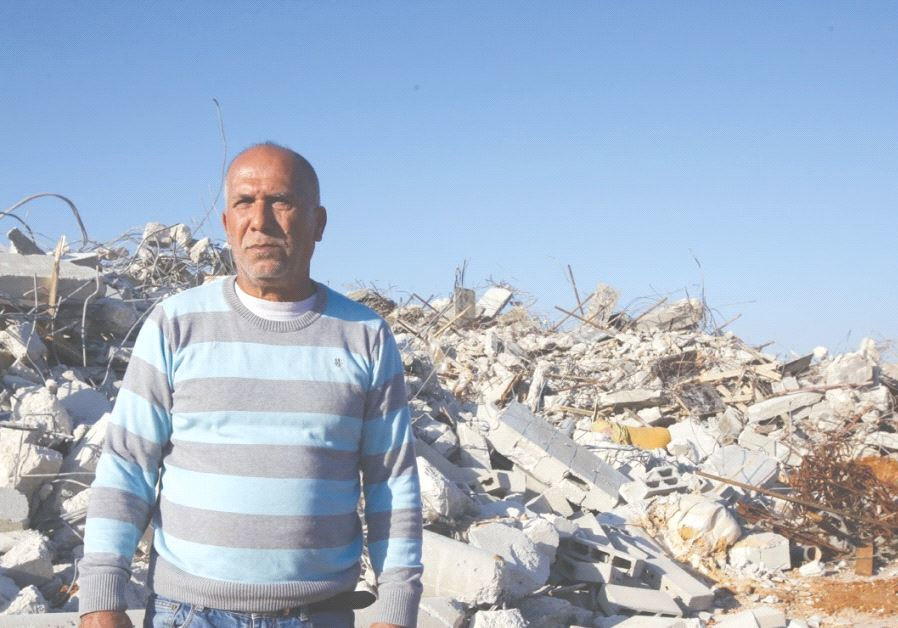 KALANSUWA RESIDENT Yusuf Makhlouf poses yesterday before the rubble of one of the 11 illegally built