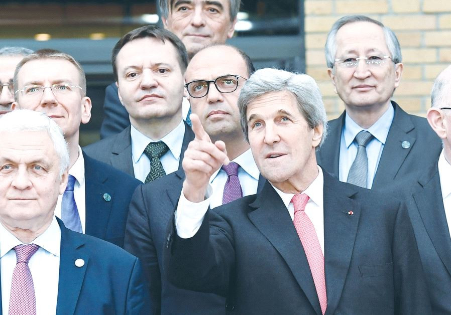 John Kerry standing among foreign ministers at Paris peace conference