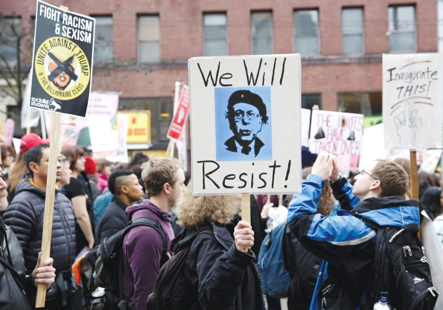 PROTESTERS HOLD up a sign urging people to 'resist' Donald Trump.