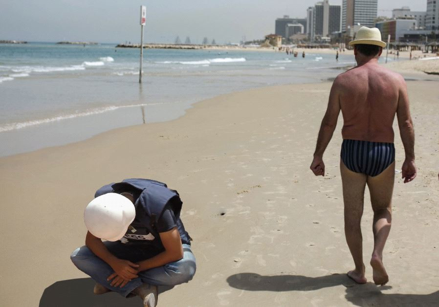 CONFLICT JOURNALIST Bob Worthington III breaks down on Tel Aviv beach as some of the 'natives' strol