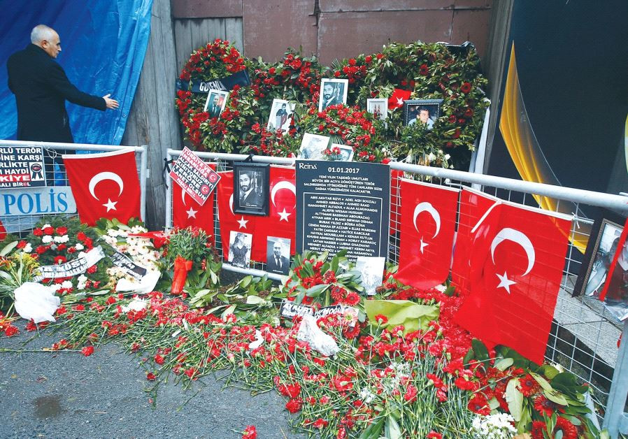 FLOWERS AND PICTURES of the victims of a terrorist attack are placed near the entrance to Istanbul's