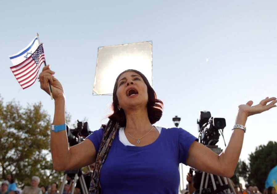A worshiper, holding an American and an Israeli flag, prays during The Day of Prayer for the Peace.