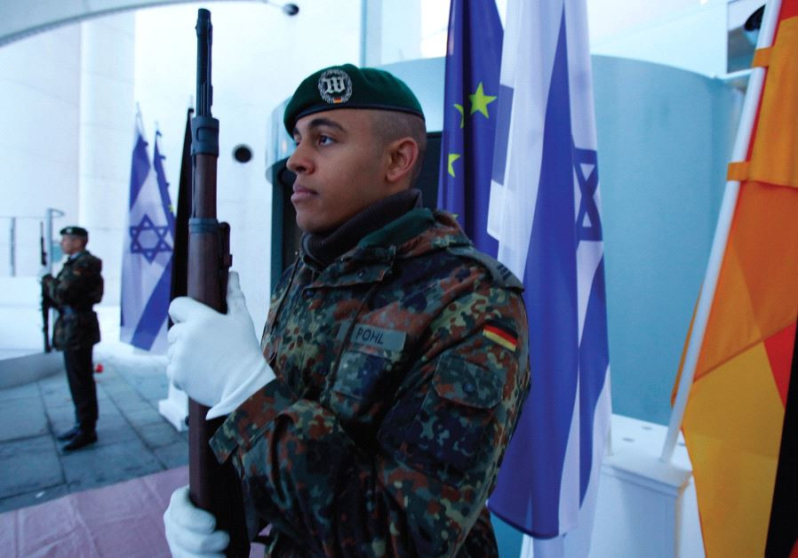 THE NEW normal. German soldiers stand guard next to Israeli, German and EU flags at the Chancellery