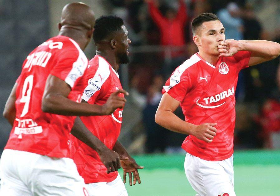 Hapoel Beersheba midfielder Ovidiu Hoban (right) celebrates with teammates Anthony Nwakaeme (9) and