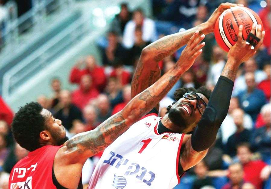 Hapoel Jerusalem center Amar'e Stoudemire (right) is smothered by Hapoel Gilboa/Galil's Eric Griffin
