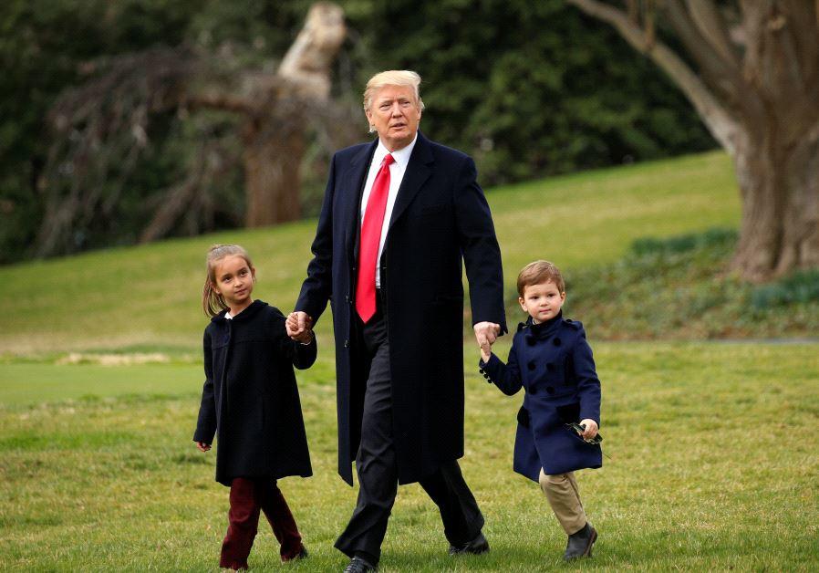 U.S. President Donald Trump holds hands with grandchildren Arabella and Joseph Kushner