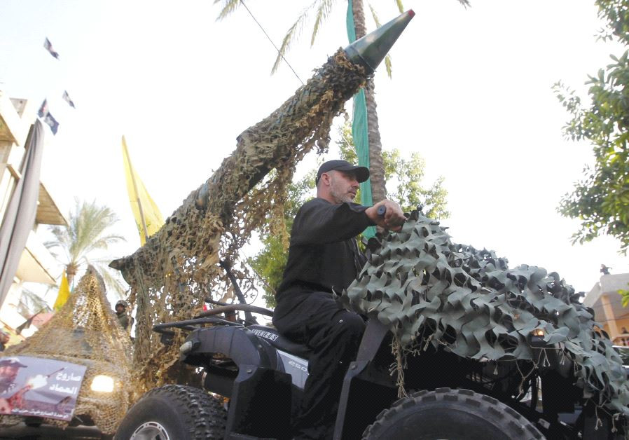 A Hezbollah member drives a 4-wheel motorbike mounted with a mock rocket in southern Lebanon in 2015
