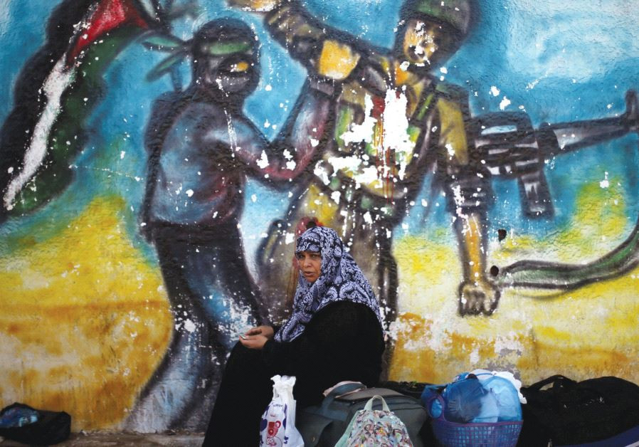 A WOMAN sits in front of a mural as she waits for a travel permit to cross into Egypt through the Ra