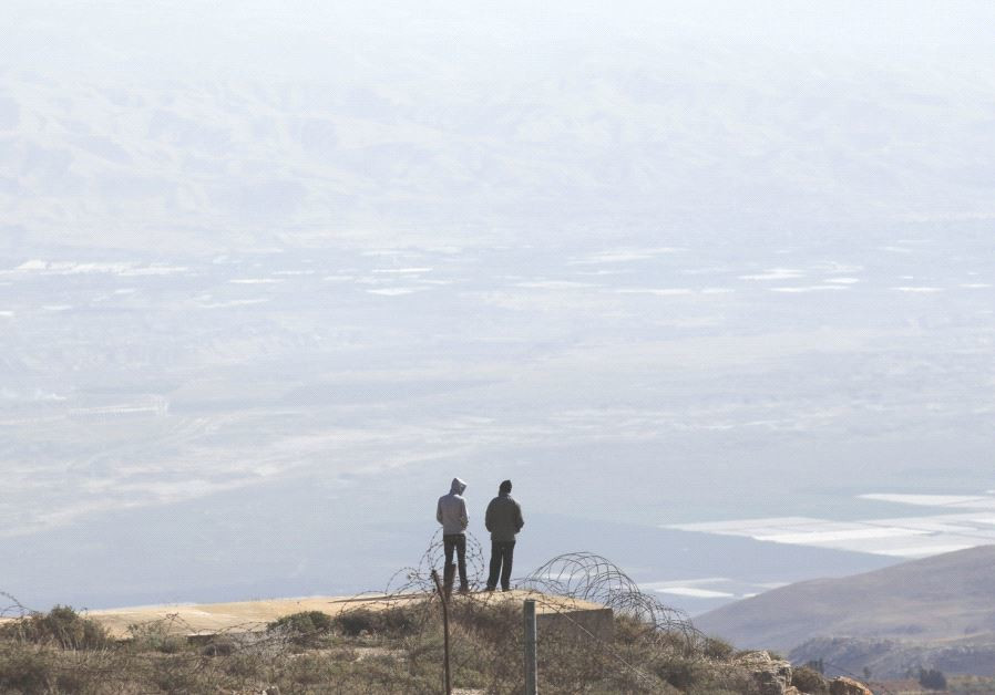 TWO SETTLERS stand atop a ridge in the West Bank.