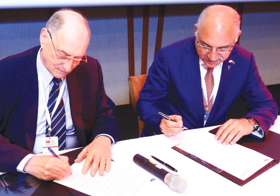 FEDERATION OF ISRAELI Chambers of Commerce board member Amnon Dotan (left) signs memorandum.