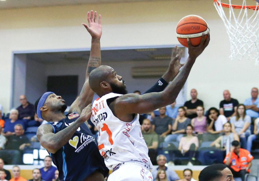 Maccabi Rishon Lezion center Charles Thomas (center) scores two of his team-high 18 points in last n