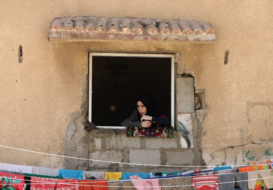 A WOMAN looks out a window in the Gaza Strip.