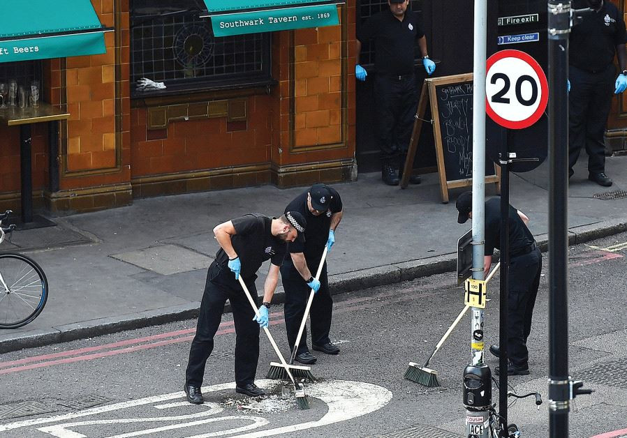 POLICE OFFICERS sweep the street outside a restaurant in Borough Market, near the scene of the recen
