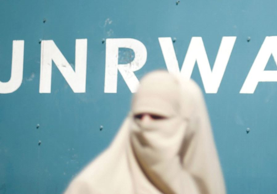 A veiled Muslim woman stands in front of a UNRWA sign