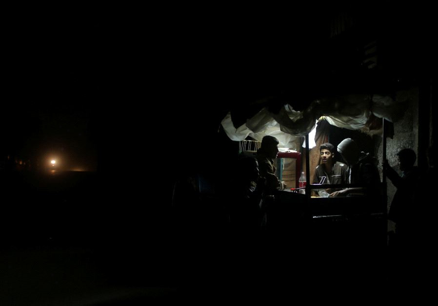 A Palestinian man sells falafel in a makeshift shop lit with a lamp powered by a battery during a po