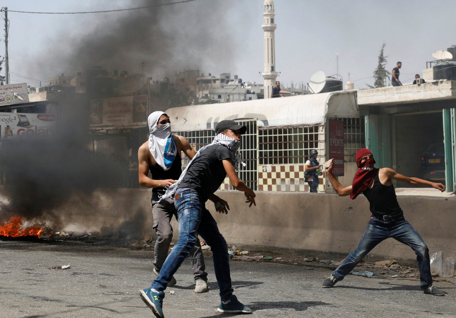 Palestinian protesters hurl stones towards Israeli troops during clashes near Qalandiya checkpoint n