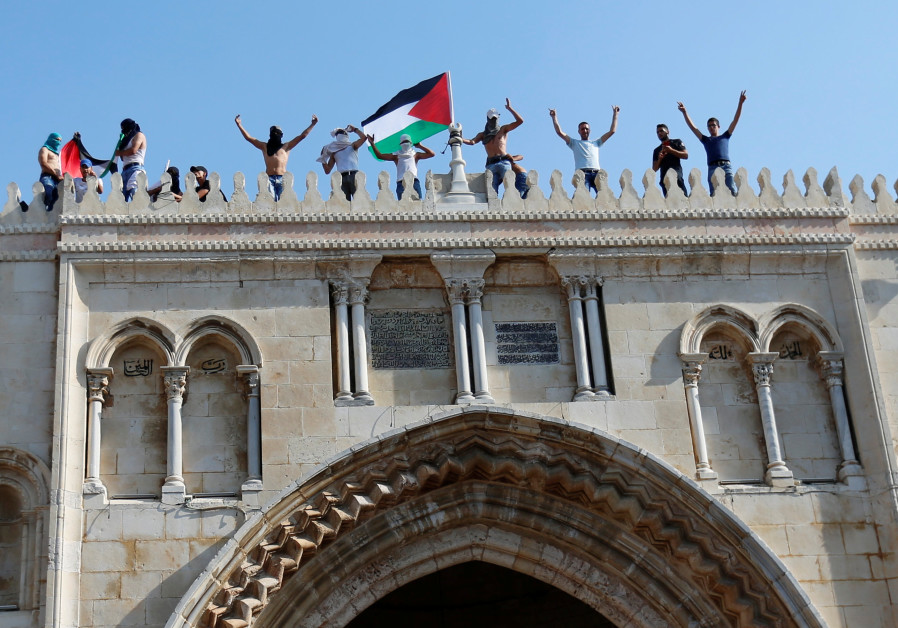 A Palestinian flag is waved at the Temple Mount in Jerusalem's Old City
