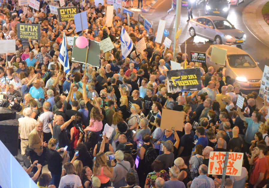 A crowd holds a rally against political corruption near the Attorney General's home in Petah Tikva