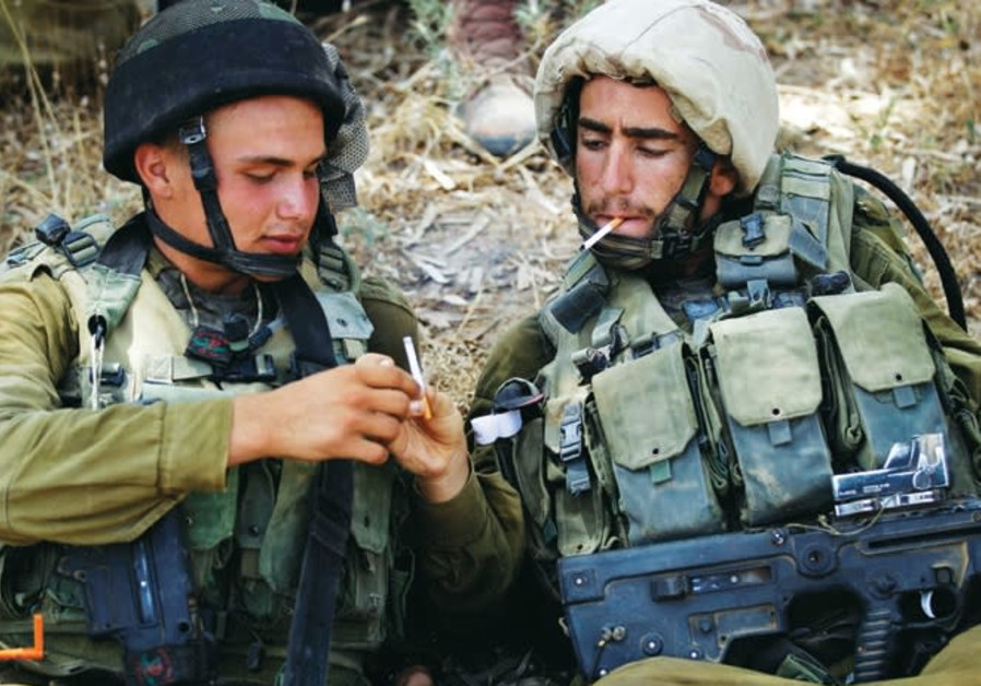IDF soldiers share cigarettes while resting in the shade near the central Gaza Strip in July 2014.