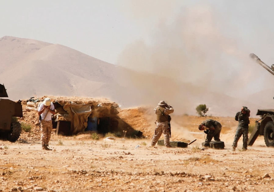 HEZBOLLAH FIGHTERS stand near military tanks in Western Qalamoun in Syria
