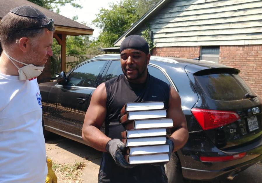 Houston resident Adrian holds his holy books while speaking with Josh Wander, a volunteer from Israe