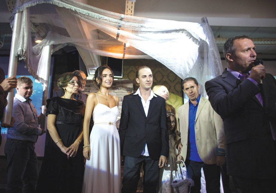 A couple stands underneath a 'huppa' during their secular wedding ceremony in Tel Aviv.