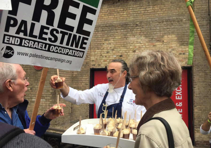 CHEF SHAUL Ben Aderet offers chocolate mousse to BDS protesters outside the Roundhouse Theatre.
