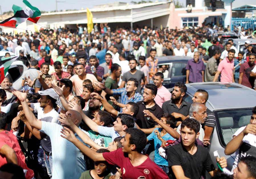 Palestinians celebrate the arrival of Palestinian Authority Prime Minister Rami Hamdallah and his go