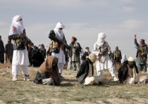 Taliban insurgents stand over three men before executing them