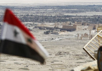 A Syrian national flag flutters as the ruins of the historic city of Palmyra are seen in the backgr