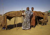 A Bella woman stands behind her Tuareg master at a camp for Malian refugees in Goudebou