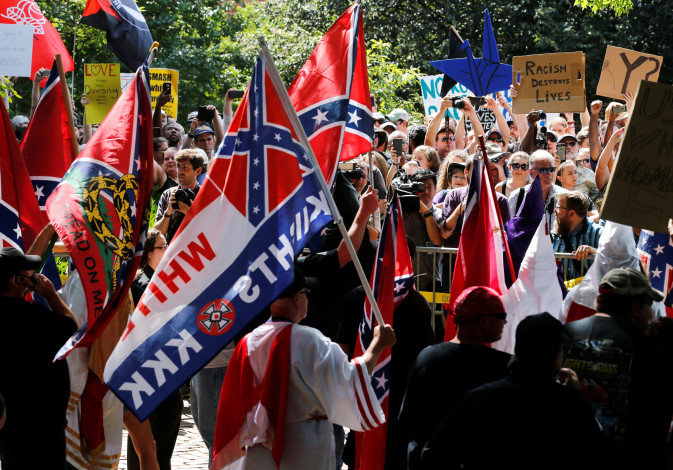 Members of the Ku Klux Klan face counter-protesters as they rally in support of Confederate monument