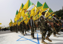 Iraqi Shi'ite Muslim men from the Iranian-backed group Kataib Hezbollah wave the party's flags