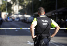 A Spanish police officer looks over a street in Barcelona after a van ramming attack there killed 13