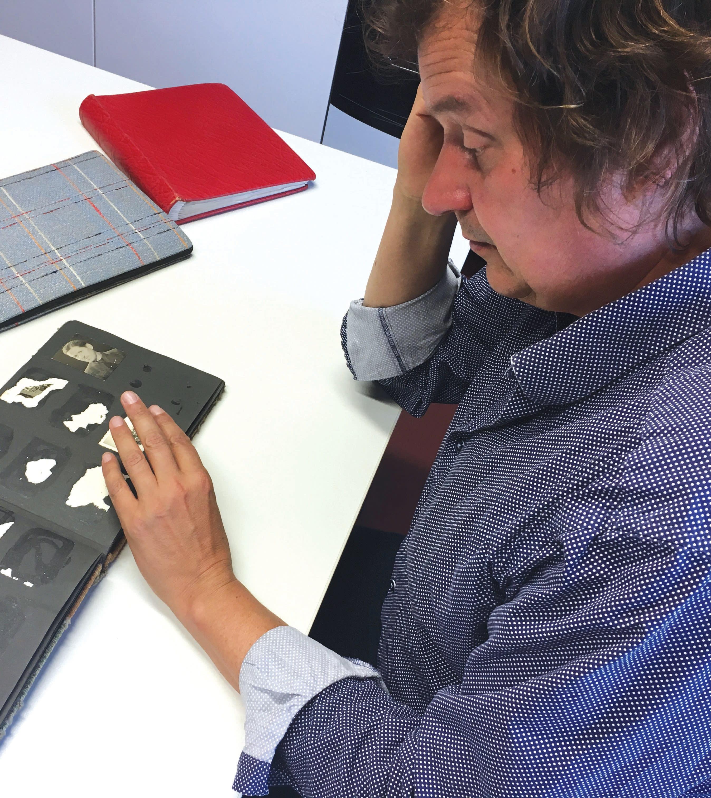 Christoph Kreutzmueller views old albums (Orit Arfa)
