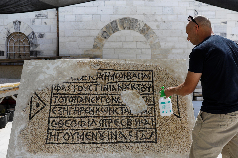 Um conservacionista trabalha em um piso de mosaico de 1500 anos com uma escrita grega, descoberta perto do portão de Damasco na cidade velha de Jerusalém, 23 de agosto de 2017 (Reuters / Ronen Zvulun)