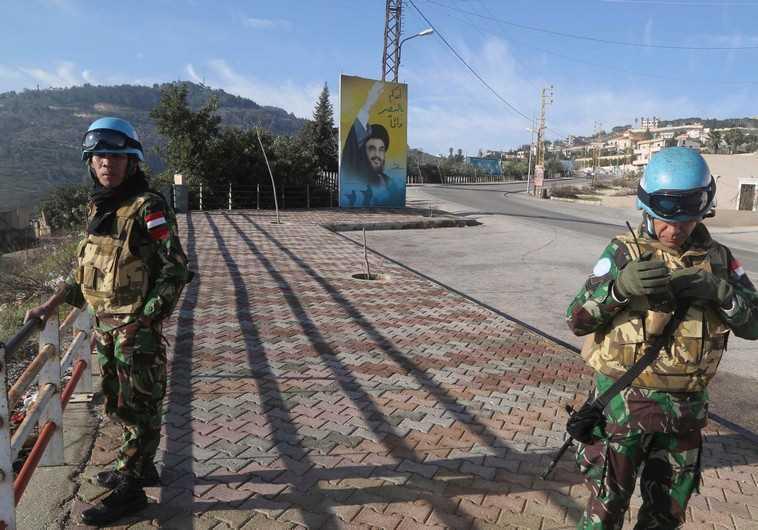 UNIFIL members beside a banner for Hezbollah leader Sayyed Hassan Nasrallah in south Lebanon (Reuters)